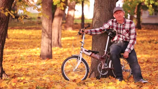 Man sit near  bicycle  in l autumn park with yellow leaves  and smile.