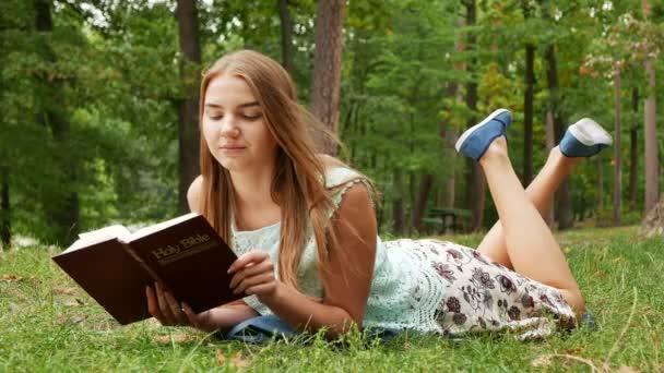 4 k. pokládání štíhlounkou dívku číst Bibli v parku a úsměv. Větrný den
