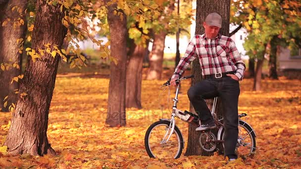 Adult man stand near  small bicycle  in  autumn park with yellow trees