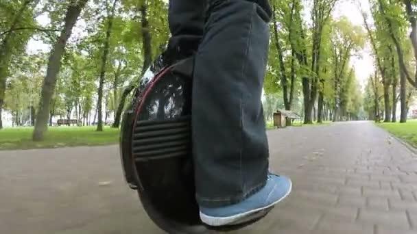 Nohy člověka na mono kolo, osobní elektrické dopravy v podzimním parku. Zadní pohled na klip POV