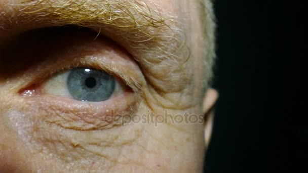 An eye of  old man with red capillaries.