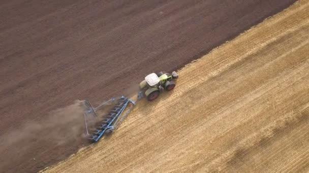 4k Aerial. Traktor s pluhem na poli. Zemědělský pracovní tým, pohled shora