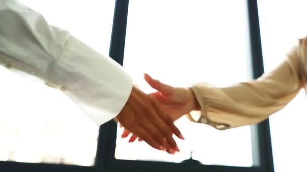 Zpomal. Dvě obchodní partnerky si potřesou rukou při schůzce v kanceláři