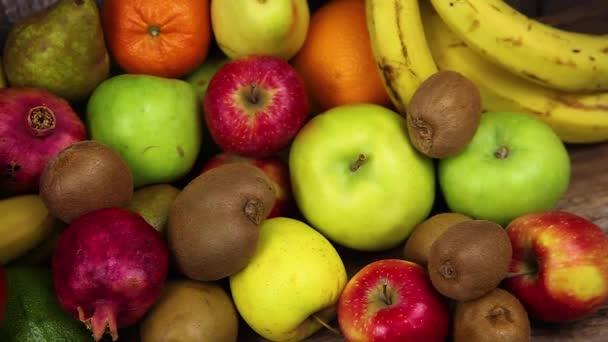 Sada různých druhů ovoce na dřevěném kuchyňském stole. Banány, manga, jablka, avokáda, kiwi, granátové jablko, mandarinky, pomeranče, hrušky. Vitamínové jídlo. Vegetariánství. Vegan Food.