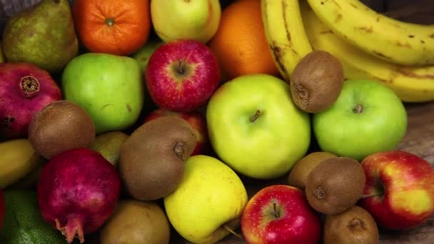 Set of different fruits on a wooden kitchen table. Bananas, mangoes, apples, avocados, kiwi, pomegranate, tangerine, orange, pears. Vitamin food. Vegetarianism. Vegan Food.