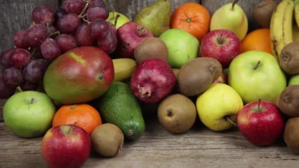 Különböző gyümölcsök egy fa konyhaasztalon. Banán, mangó, alma, avokádó, kivi, gránátalma, mandarin, narancs, körte. Vitaminok. Vegarianizmus. Vegán Élelmiszer.
