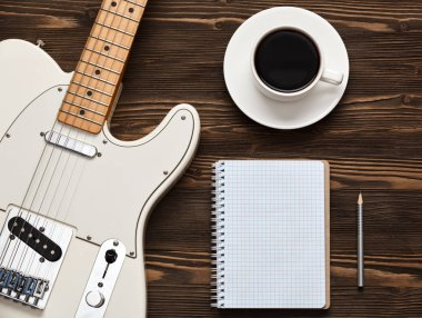 Coffee cup and guitar on wooden table.