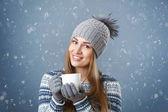 Krásná usměvavá dívka drží pohár s horkým nápojem.