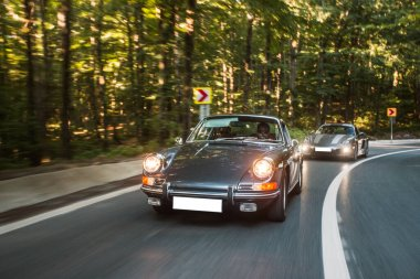 Followed by a black vintage car on the forest road
