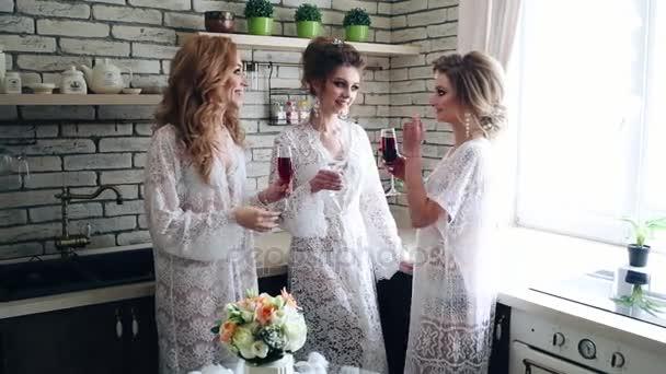 Mladé dívky v bílém budoár pít víno v kuchyni