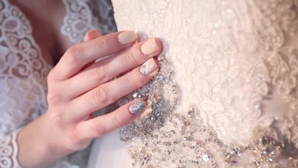 Ruce v bílých svatebních šatech