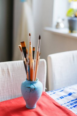 Paint Brushes on a table. Vertical photo. Artists workshop.