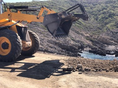 Yellow loader backhoe is planning a road surface during road construction works. Earthmoving, excavations, digging