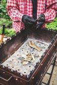 Fotografia uomo sta per costruire la fiamma nel braciere in metallo
