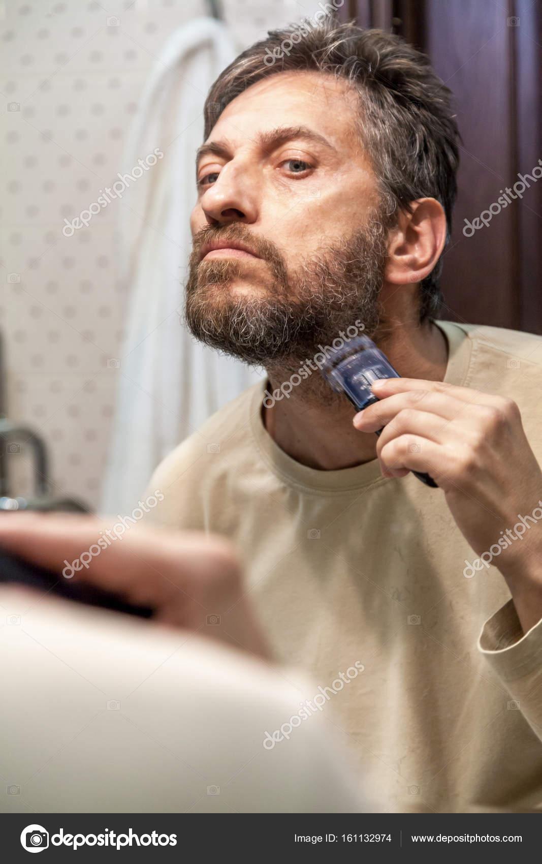 En trevlig Herre i en beige T-shirt skeva själv sitt grå skägg med hjälp av  maskiner innan en stor spegel i badrum — Foto av glebchik 0ebfe98f5e183