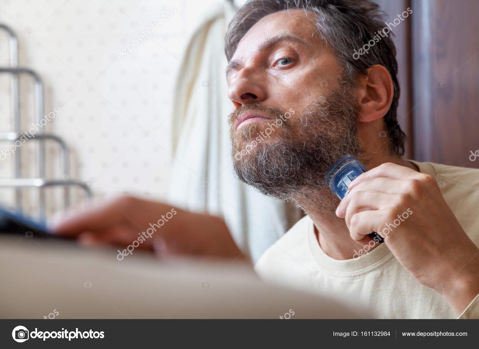 En trevlig Herre i en beige T-shirt skeva själv sitt grå skägg med hjälp av  maskiner innan en stor spegel i badrum — Foto av ... 25f100ecf970b
