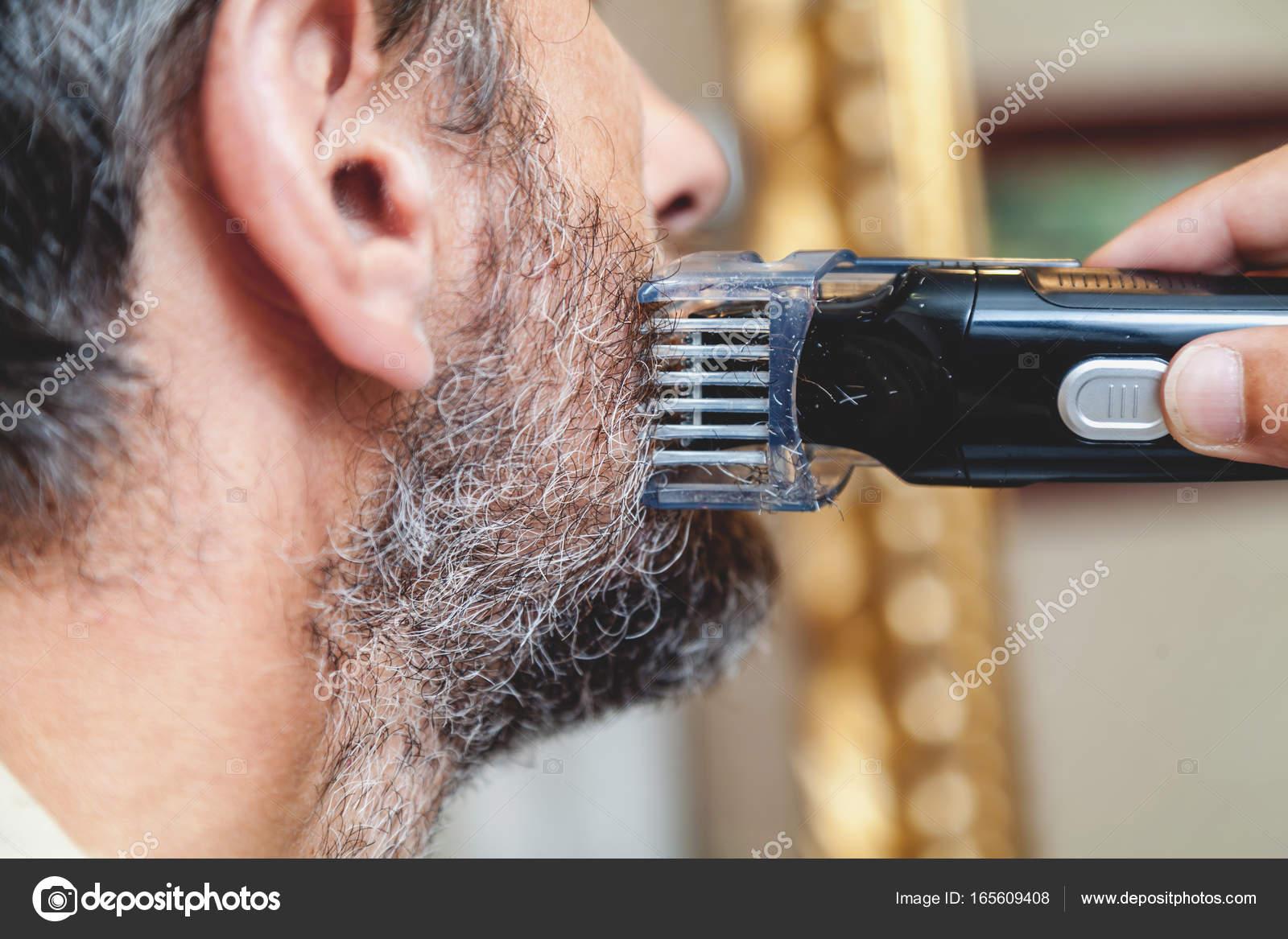 Man klipper sin egen grå skägg med en skrivmaskin-closeu — Foto av glebchik a267f8168d2a6