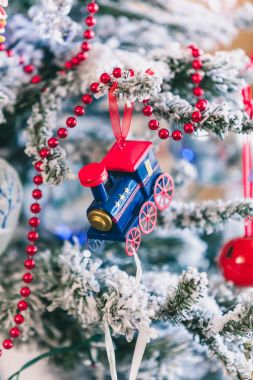 blue little steam engine weighs on Christmas tree