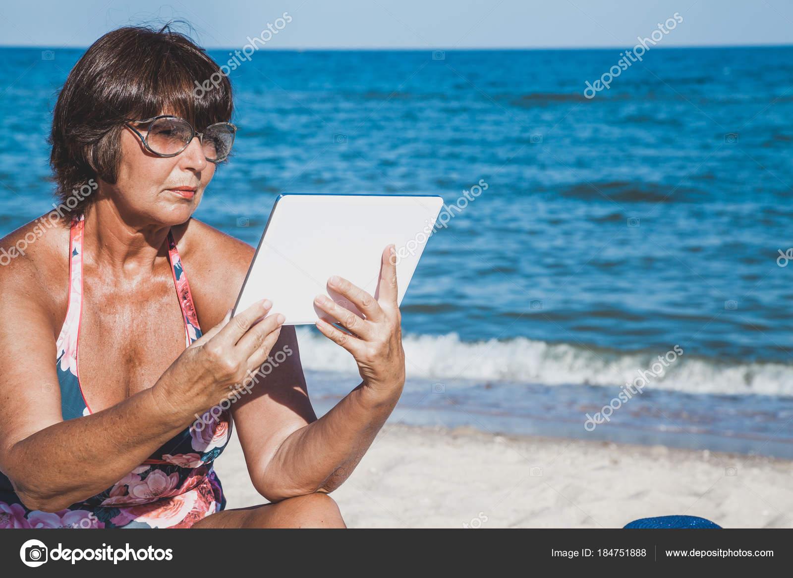 0e5a636497e5 Donna anziana in un costume da bagno, prendere il sole e che tiene una  compressa sulla spiaggia del mare di estate — Foto di ...