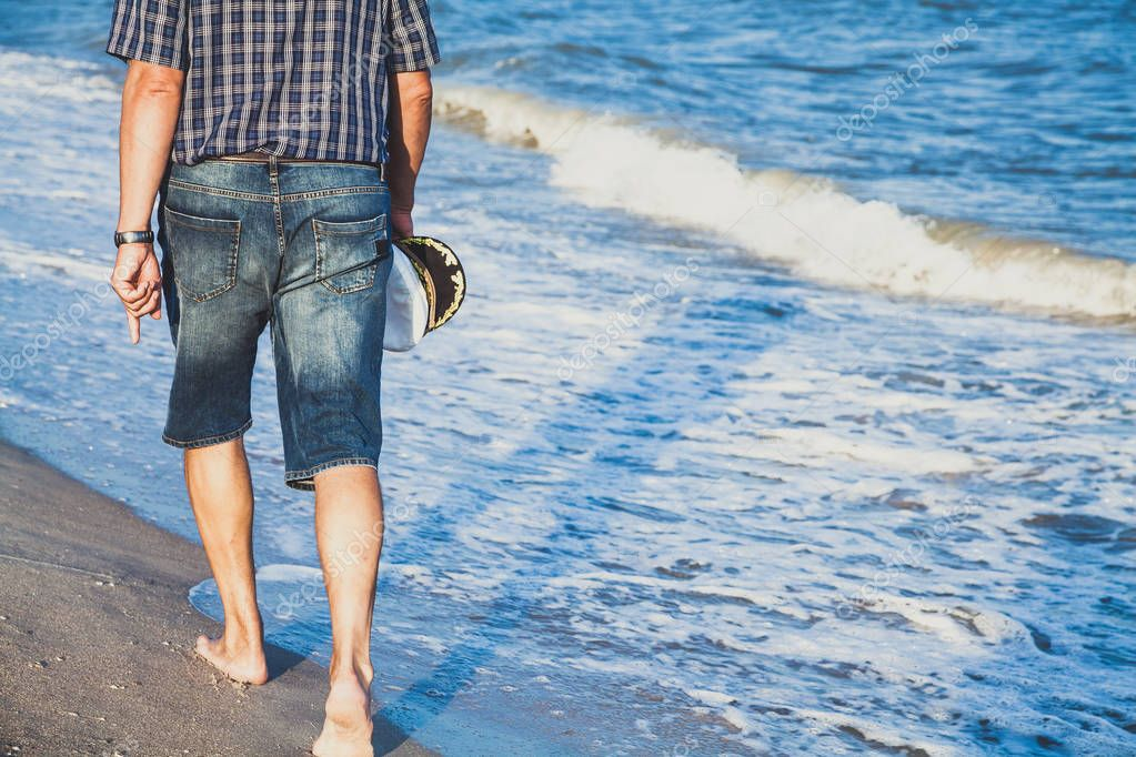 Man walks on the sea beach
