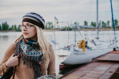 slender blonde in beret stands next to yacht