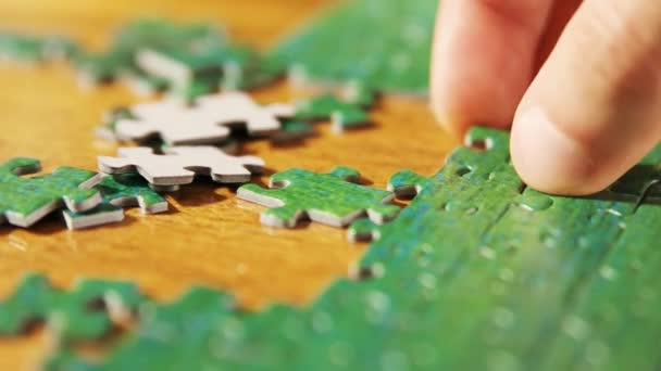 Caucasian male hands disassembling jigsaw puzzle. Single pieces and complete puzzle at background. Warm colors