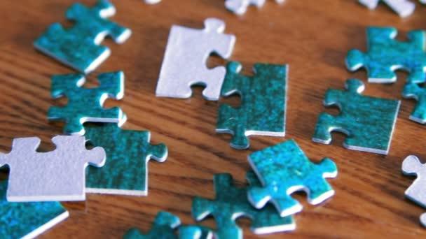 Panning z puzzle kousky dokončit puzzle. Modré kousky na dřevěném stole