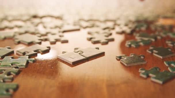 Caucasian male hands assembling jigsaw puzzle pieces. Single pieces and complete puzzle at background. Warm colors