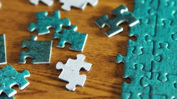 Slow panning from complete puzzle to puzzle pieces. Blue pieces on wooden table