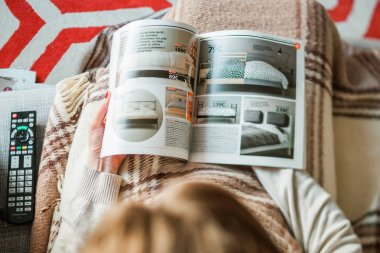 Woman reading IKEA catalog buying beddings for bedroom