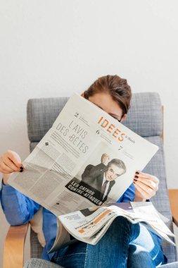 Woman reading Le Monde about Francois Fillon presidential candid
