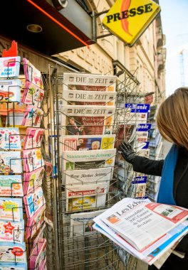 Woman purchases US press newspaper from a newsstand