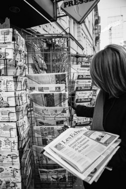 Woman purchases a USA TODAY WEEKEND newspaper from a newsstand