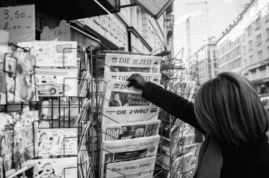 Woman purchases a Die Zeit german newspaper from a newsstand