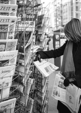 Woman purchases a Le Monde French Press newspaper from a newssta