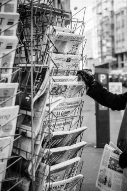 Woman purchases a le canard enchaine, l'alsace,la croiz, charlie