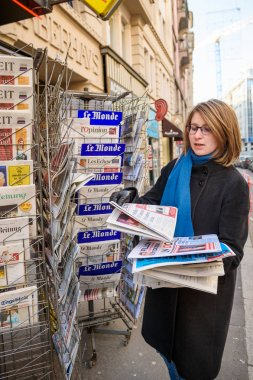Woman purchases interantional press from a newsstand