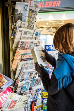 Woman purchases a Wall Street Journal newspaper from a newsstand