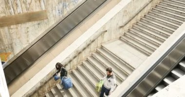 people using escalator and stairs