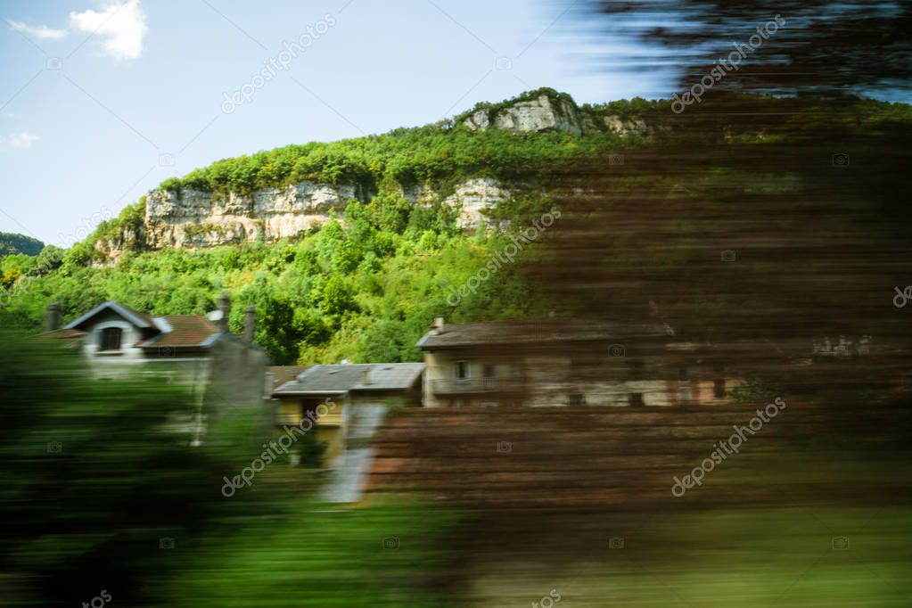 Alps mountains and hidden house seen from fast train in motion