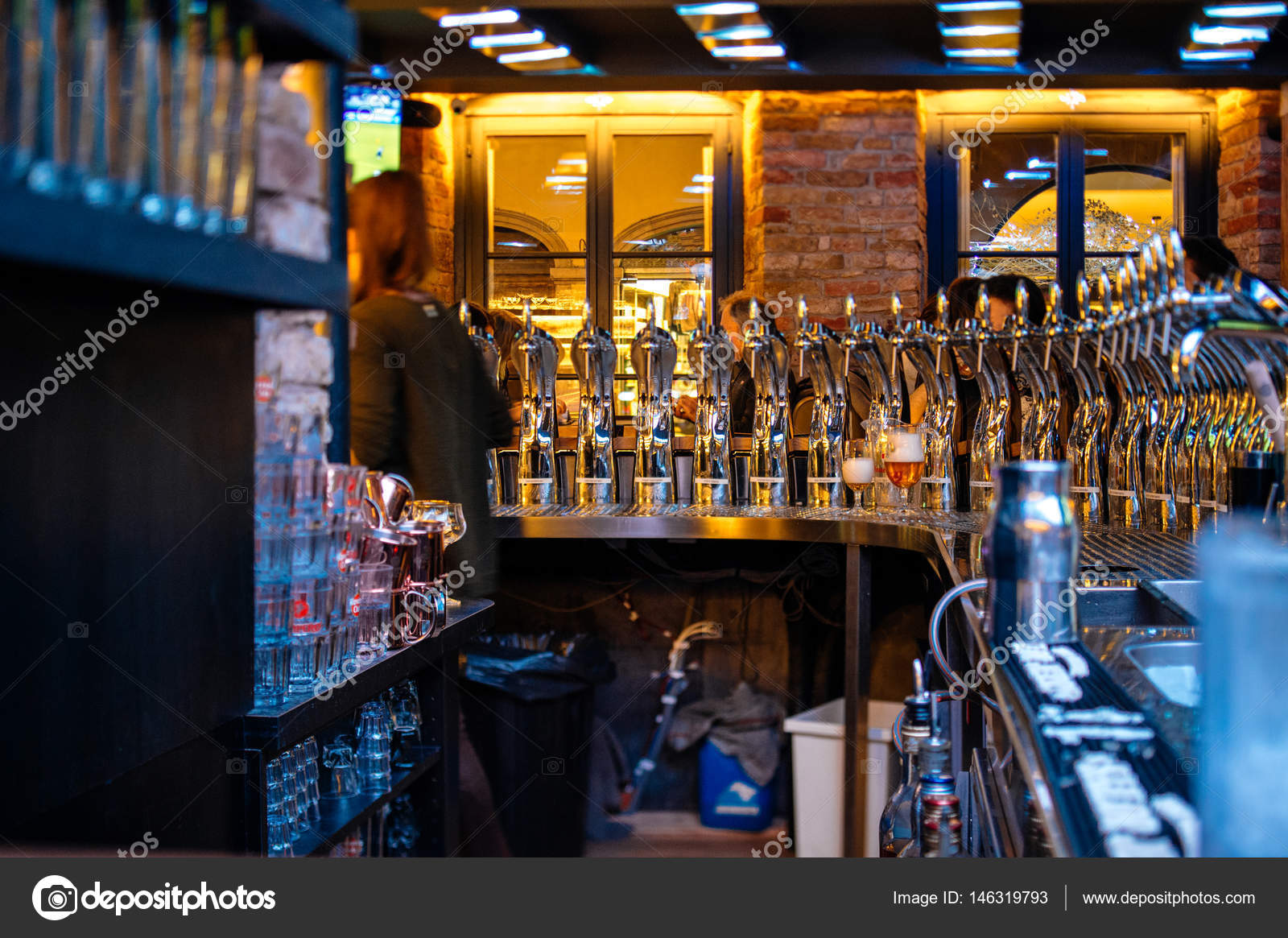 Beer taps inside beer pub bar with silhouette of visitors having ...