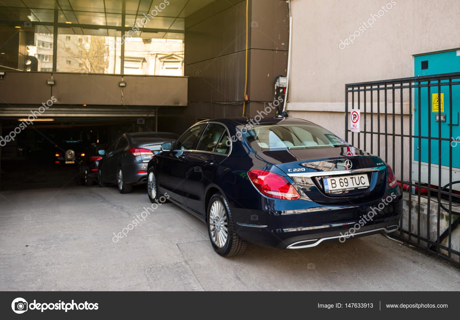 mercedes-benz c-klasse geparkt vor große garage tor — redaktionelles