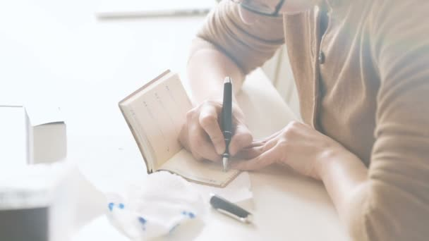 Closeup of woman writing in notebook agenda her personal schedule appointment with old vintage fountain pen