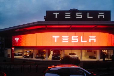 Tesla motors showroom with cars inside and illuminated logo bran