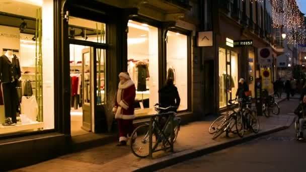 Santa s lidí, kteří jdou na ulici s budovami v noční době