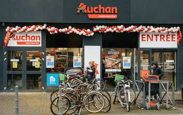 STRASBOURG, FRANCE - December 4, 2017: Auchan Supermarket entrance in French neighborhood on a winter snow day with customers exiting the entrance of the store