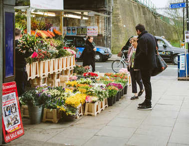 LONDON, UNITED KINGDOM - March 10 2017: Couple buying flowers at flower florist kiosk on the street in London early in the morning