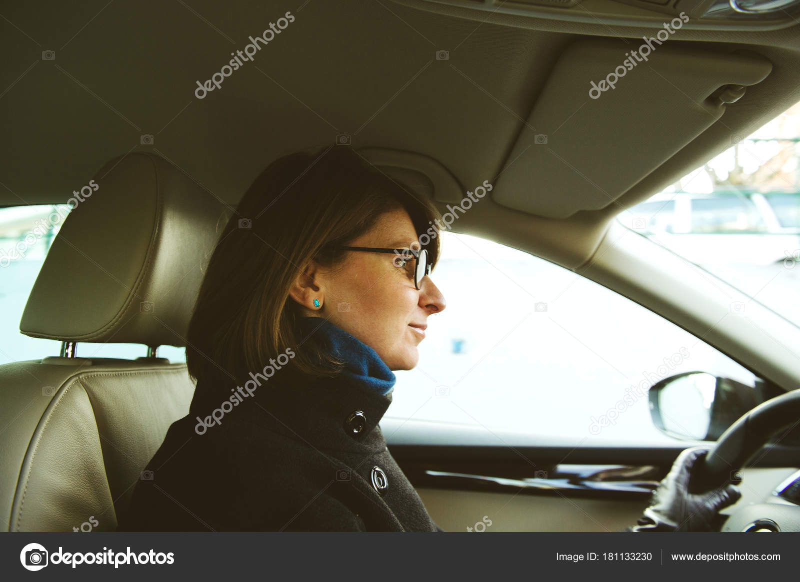 Confident Young Woman Driving Luxury Car Leather Interior Stock