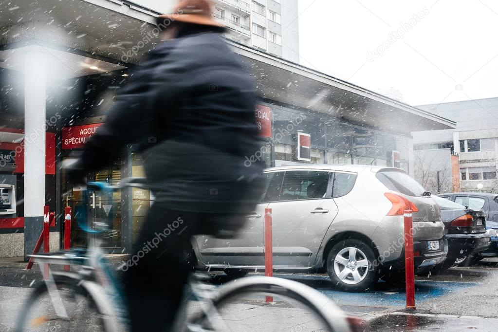 Snowy day in France with senior man on bicycle on the street