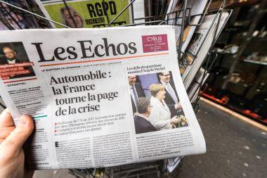 Man reading buying French Les Echos newspaper at press kiosk fe